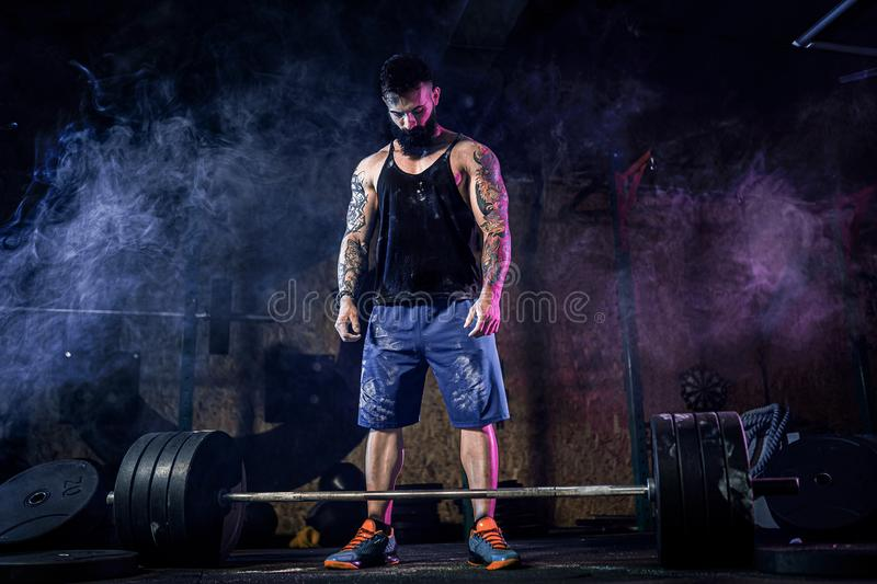 Muscular fitness man preparing to deadlift of a barbell in modern fitness center. Functional training. stock photo