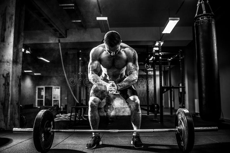 Muscular fitness man preparing to deadlift a barbell over his head in modern fitness center.Functional training. stock photography