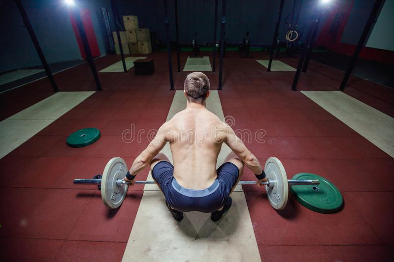 Muscular fitness man preparing to deadlift a barbell over his head in modern fitness center.Functional training.Snatch royalty free stock photos