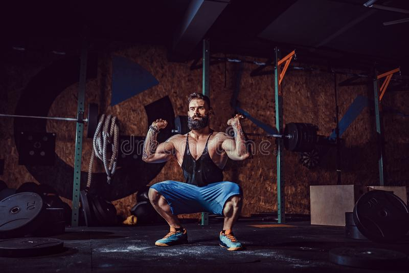 Muscular fitness man preparing to deadlift a barbell over his head in modern fitness center. Functional training. royalty free stock images