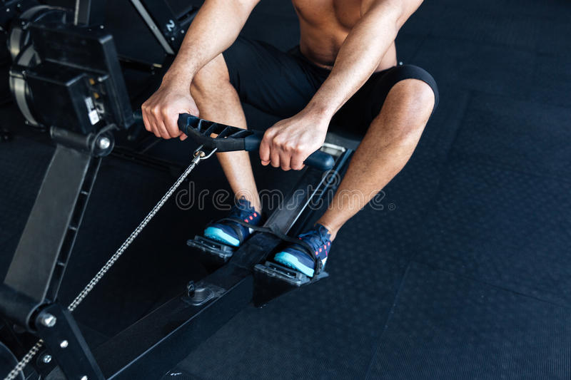 Muscular fitness man using rowing machine in the gym stock images