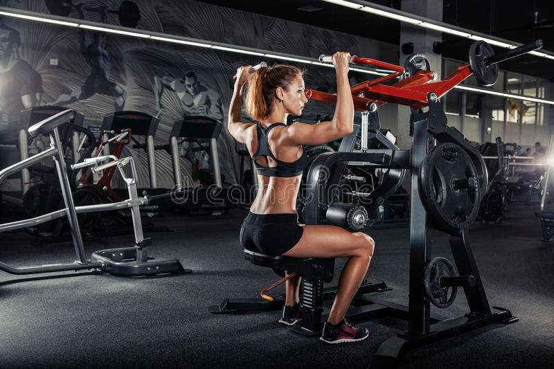 Muscular fitness woman doing exercises in the gym. stock photo