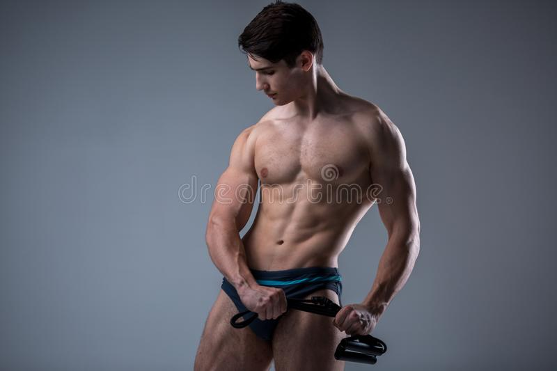 Muscular fitness young male antique perfect muscles six packs of abs and bare chest. Bodybuilder model trains with a stretching. Elastic against a dark royalty free stock photography