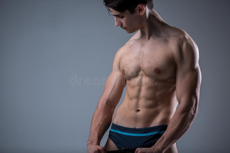 Muscular fitness young male antique perfect muscles six packs of abs and bare chest. Bodybuilder model trains with a stretching. Elastic against a dark stock image