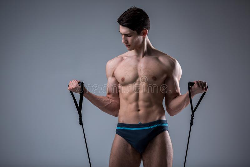 Muscular fitness young male antique perfect muscles six packs of abs and bare chest. Bodybuilder model trains with a stretching. Elastic against a dark royalty free stock image
