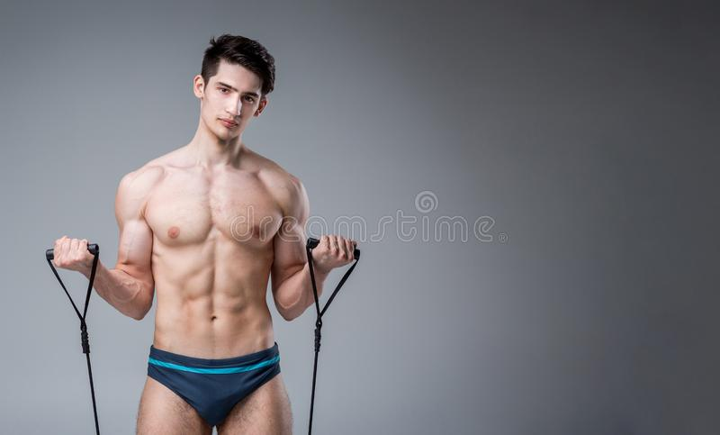 Muscular fitness young male antique perfect muscles six packs of abs and bare chest. Bodybuilder model trains with a stretching. Elastic against a dark royalty free stock images