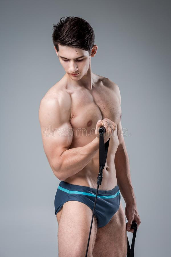 Muscular fitness young male antique perfect muscles six packs of abs and bare chest. Bodybuilder model trains with a stretching. Elastic against a dark royalty free stock photo
