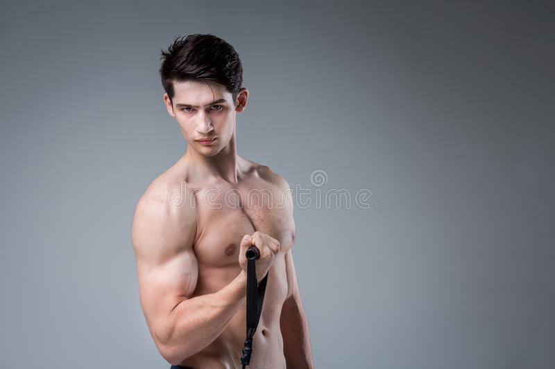 Muscular fitness young male antique perfect muscles six packs of abs and bare chest. Bodybuilder model trains with a stretching. Elastic against a dark stock photos