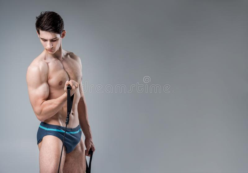 Muscular fitness young male antique perfect muscles six packs of abs and bare chest. Bodybuilder model trains with a stretching. Elastic against a dark royalty free stock photos