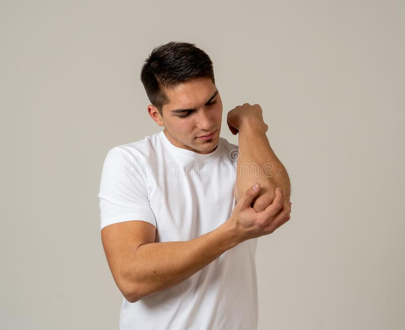 Body pain and sport injury. Strong young man suffering pain in the elbow stock photography