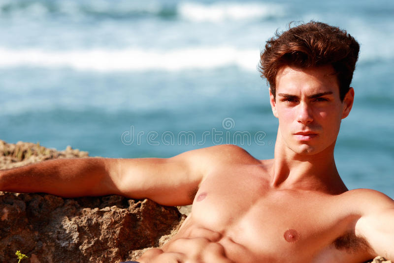 Muscular guy relaxing in the sea stock photography