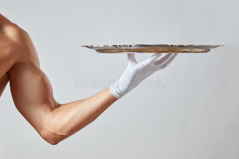 Muscular hand of waiter in a white glove holding a silver vintage empty tray on a white background. Waiter with muscular hand in a white glove holding a metal royalty free stock photography