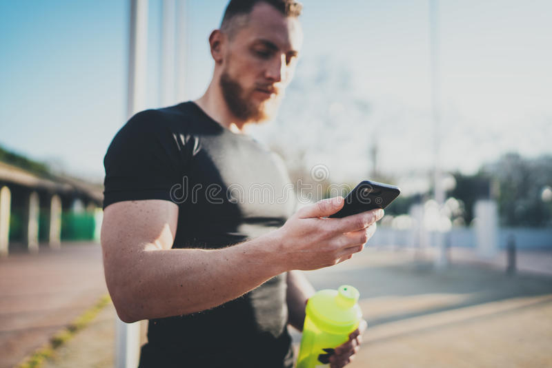 Muscular handsome athlete checking sport results on smartphone application and smart watch after good workout session on stock photography