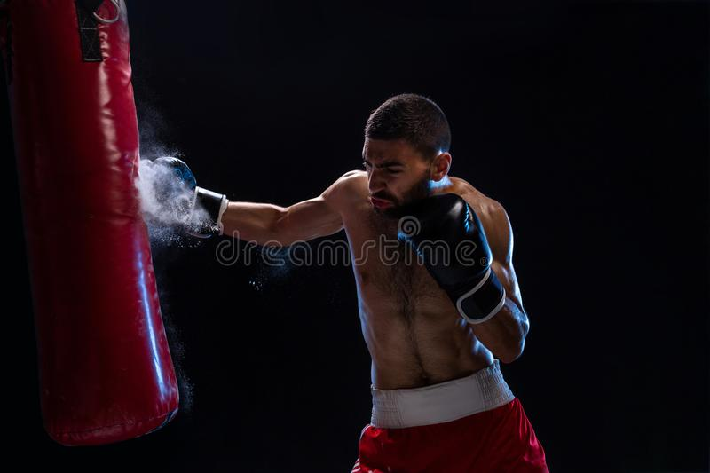 Muscular handsome boxer giving a forceful forward kick during a practise round with a boxing bag. stock photography