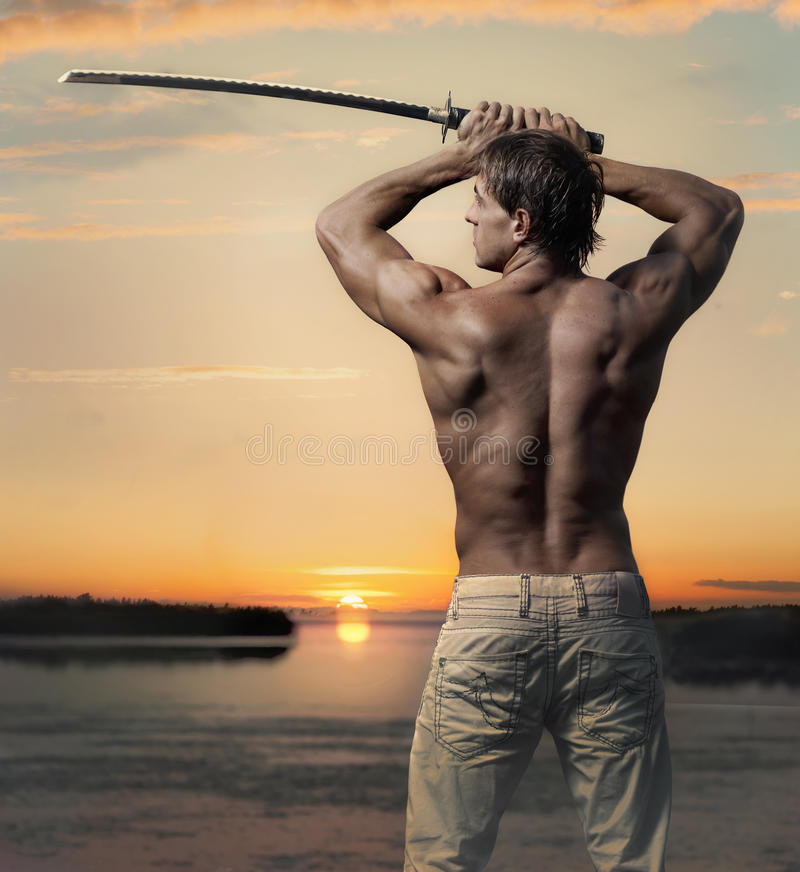 Muscular handsome guy with sword at sunset royalty free stock image