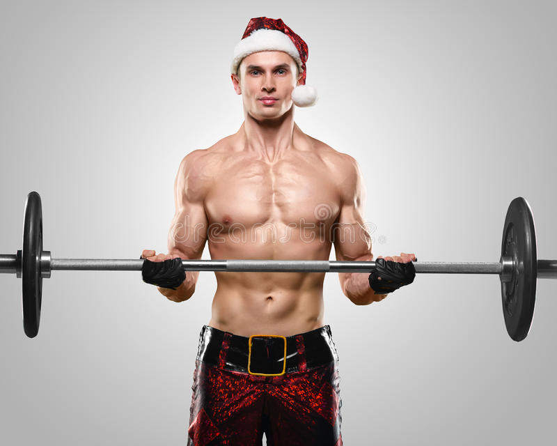 Muscular handsome Santa Claus. Holidays and celebrations, New year, Christmas, sports, bodybuilding, healthy lifestyle - Muscular handsome Santa Claus stock image
