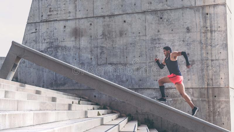 Muscular hispanic dark-skinned male athlete build running up a flight of stairs with speed.Concret background wall with. Copy space area for text message or stock photos