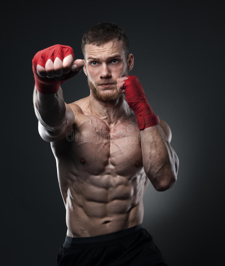 Muscular kickbox or muay thai fighter punching. Isolated, clipping path included royalty free stock image