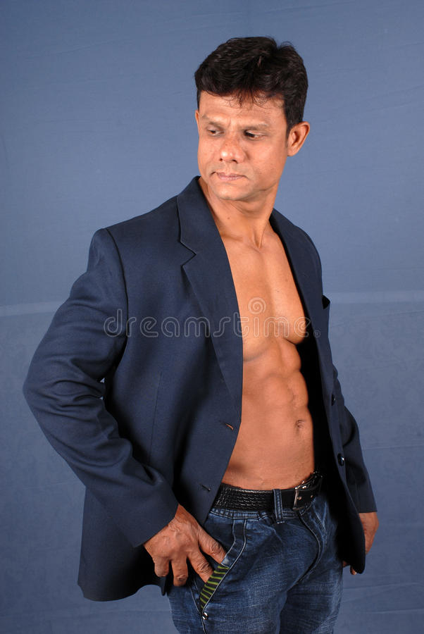 Muscular Male in Blazer. Muscular male wearing a suit jacket showing his bare chest royalty free stock photo