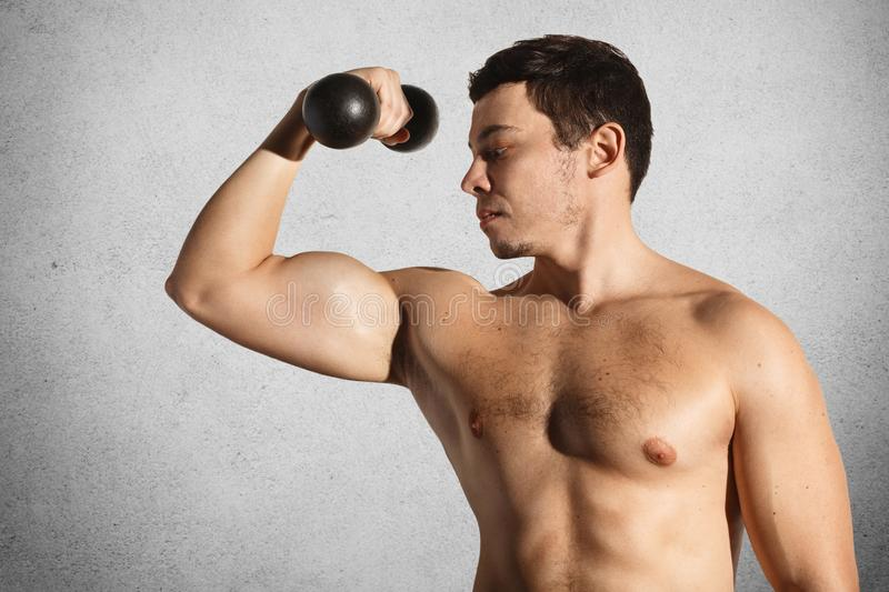 Muscular male bodybuilder demostrates his strong body, lifts dumbbell over grey concrete wall, being naked, shows muscle. Active y royalty free stock photography