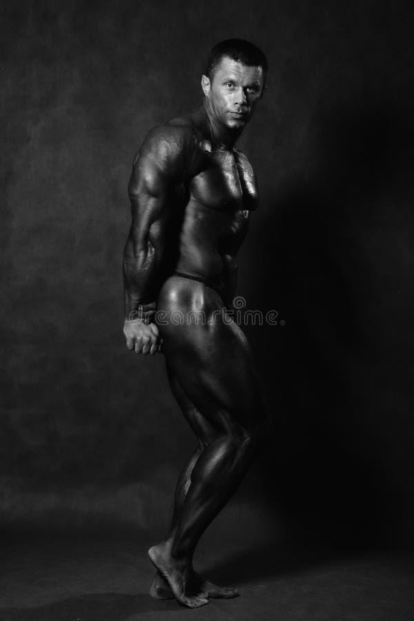 Muscular male Bodybuilder posing in studio stock images