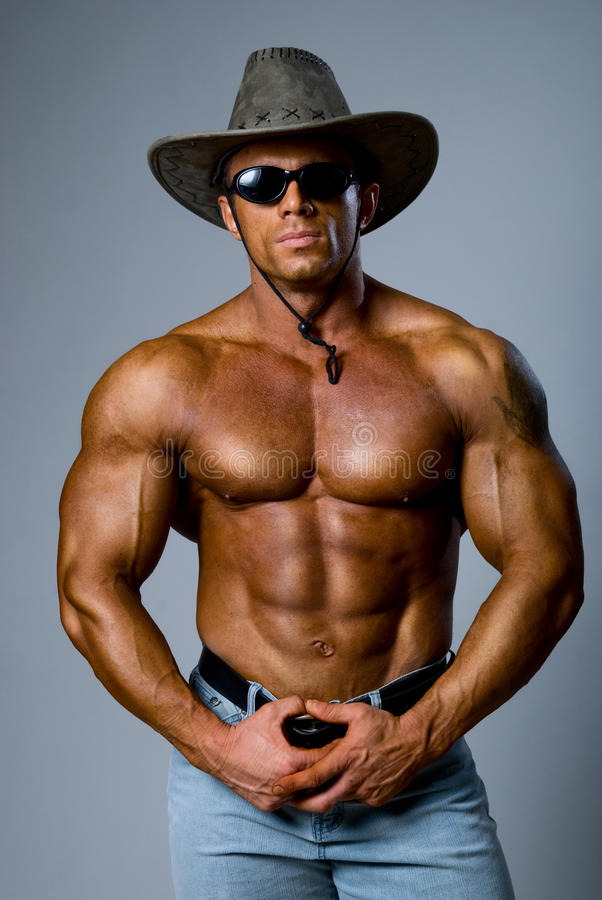 Muscular male in a hat and sunglasses royalty free stock photo
