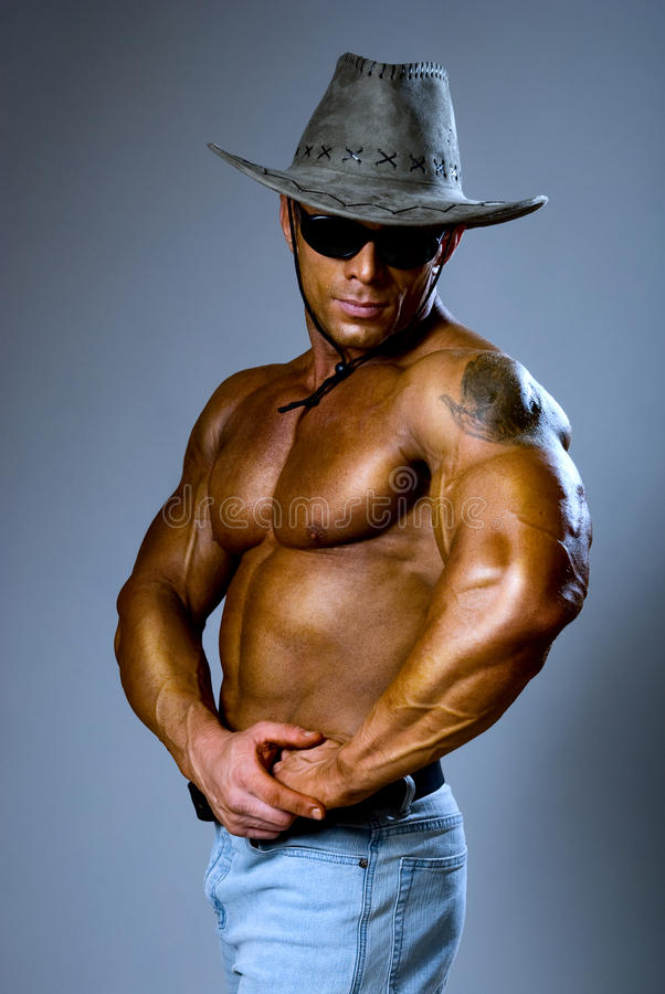 Muscular male in a hat and sunglasses royalty free stock image