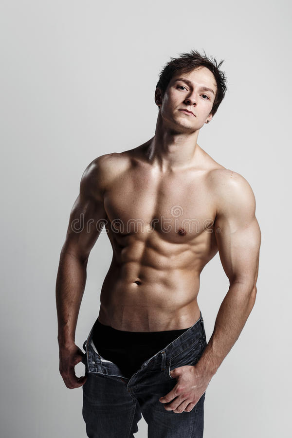 Muscular male model bodybuilder with unbuttoned jeans. Studio sh stock photos