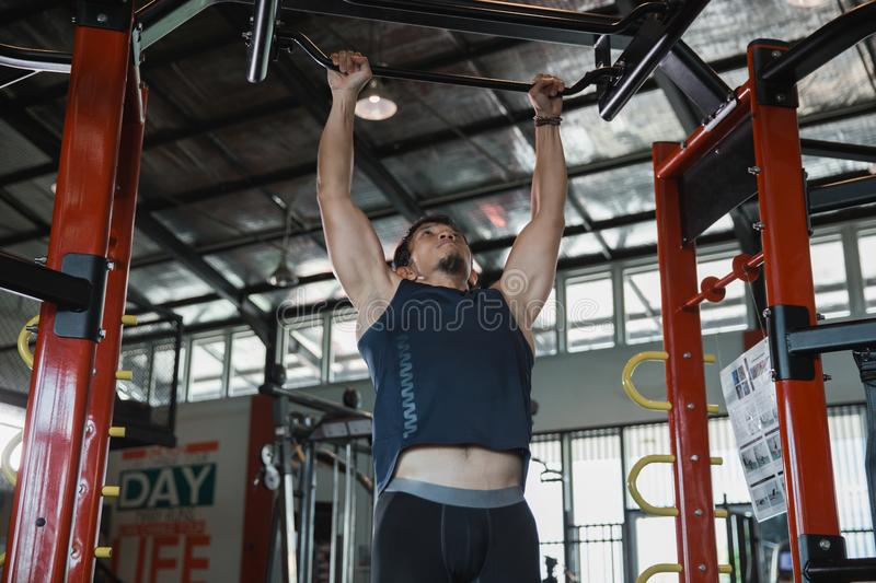 Muscular male model with perfect body doing pull ups stock photo