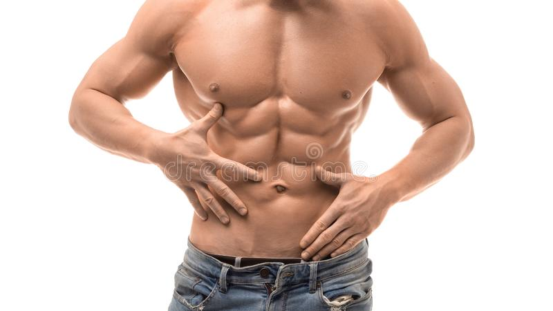 Muscular male torso isolated on white. Shirtless man in blue jaens touching his abs stock image
