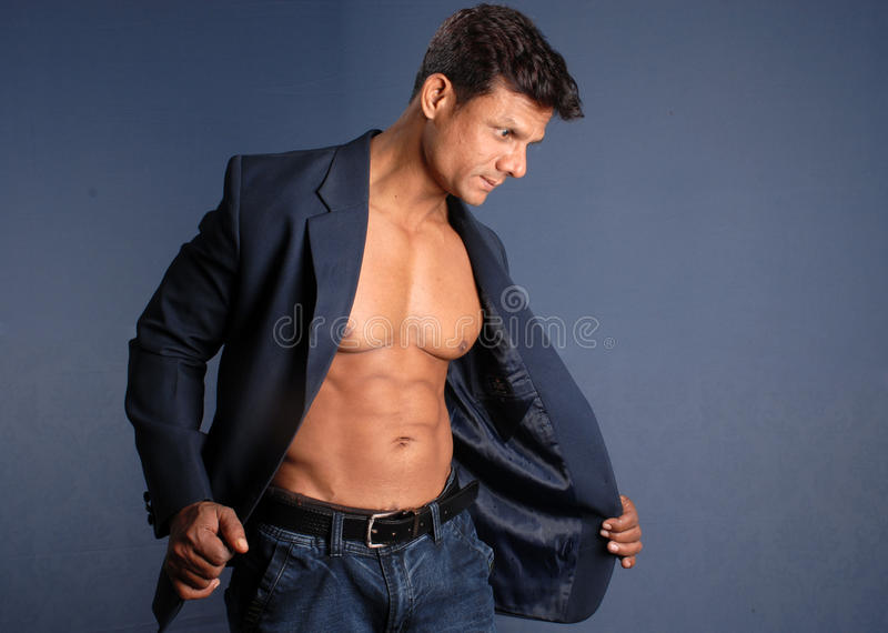 Muscular Male. Wearing a suit jacket showing his bare chest stock photography