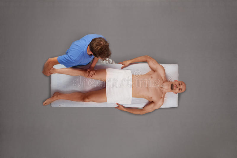 Muscular man being massaged by therapist stock photos