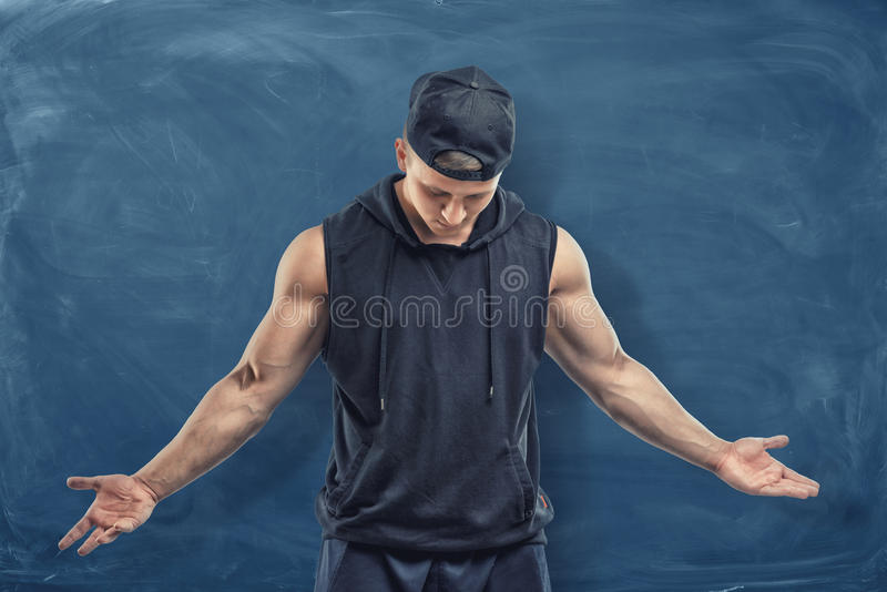 Muscular man in black clothes and cap with his head lowered on blue chalkboard background. royalty free stock photo