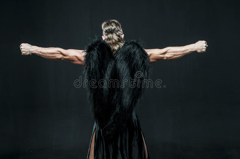 Muscular man with black wings royalty free stock image