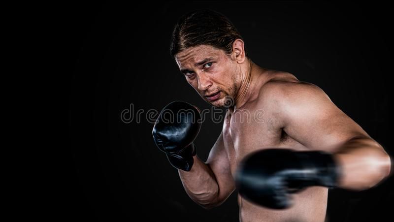Muscular man boxing with gloves. boxer punching fist movement .  Isolated on black background with copy Space. Torso, workout, thai, muay, fighter, handsome stock photography