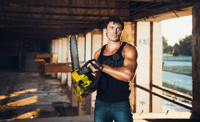 Muscular Man With A Chainsaw Stock Image