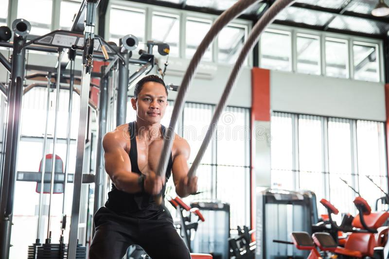 Muscular man is doing battle rope exercise stock image