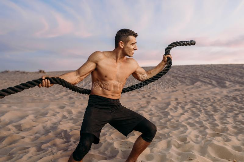 Muscular man doing exercise with rope in desert stock photography