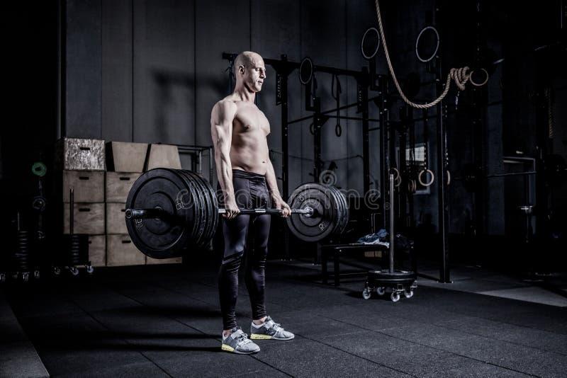 Muscular Man Doing Heavy Deadlift Exercise. Dramatic color grading. stock photos