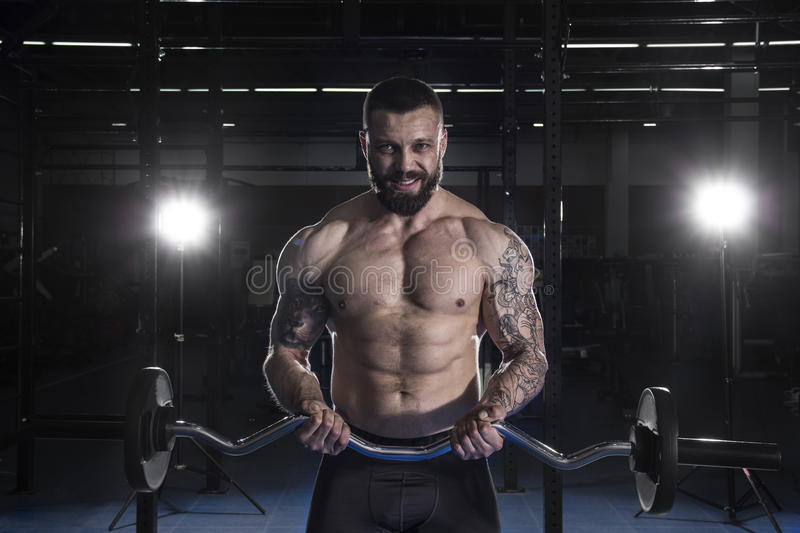 Muscular Man Doing Heavy Weight Exercise For Biceps With Barbel royalty free stock photos