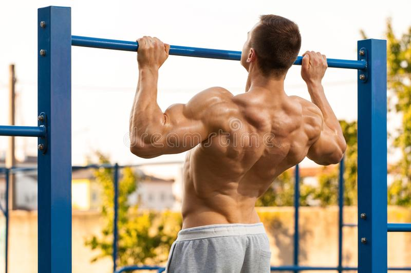 Muscular man doing pull up on horizontal bar, working out. Strong fitness male pulling up, showing back, outdoors royalty free stock photography