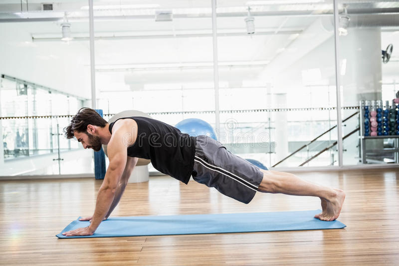 Muscular man doing push up on mat. In the studio royalty free stock photography