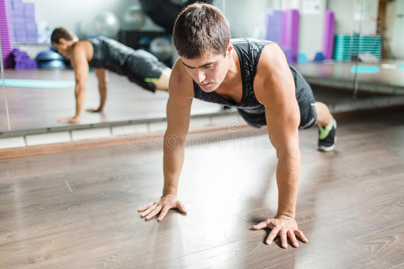 Muscular Man doing Push Ups in Fitness Studio. Portrait of strong muscular man doing push ups during workout in modern fitness studio next to mirror royalty free stock photography