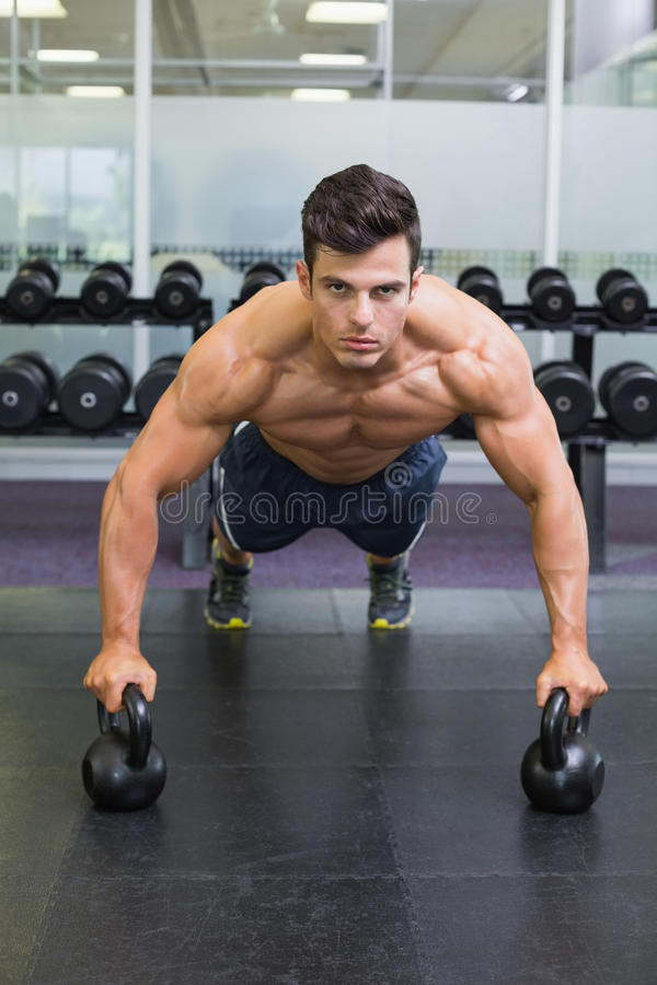 Muscular man doing push ups with kettle bells in gym. Portrait of a muscular man doing push ups with kettle bells in gym stock photos