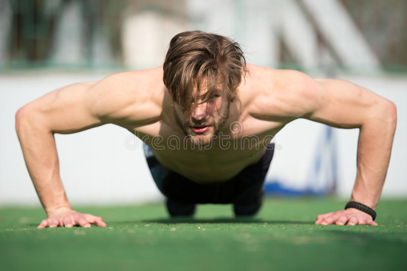 Muscular man doing push ups, male athlete exercising push up. Sunny outdoor, fit shirtless guy, fitness model exercise outside. healthy lifestyle concept stock image