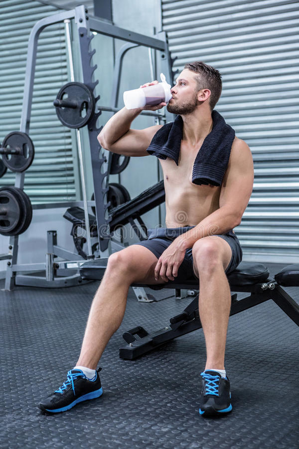 Muscular man drinking protein cocktail stock photo