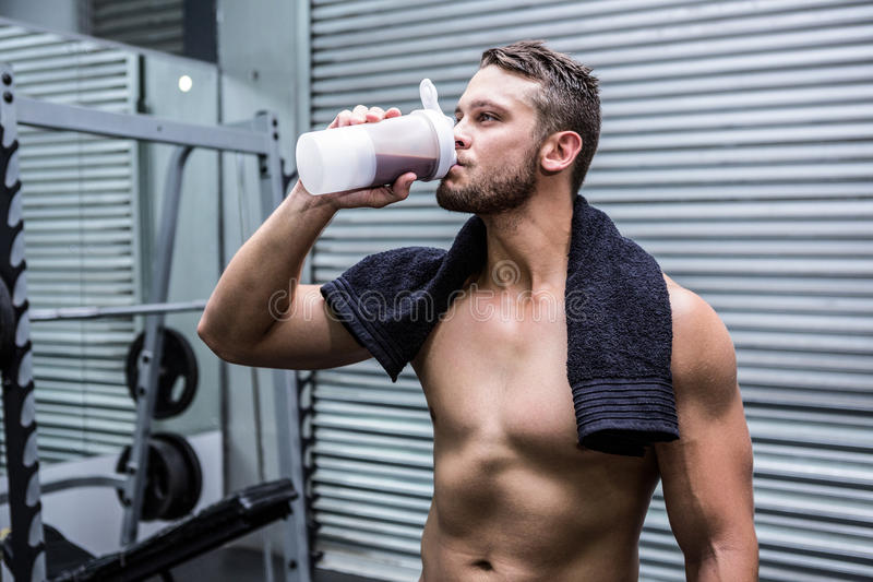 Muscular man drinking protein cocktail stock image