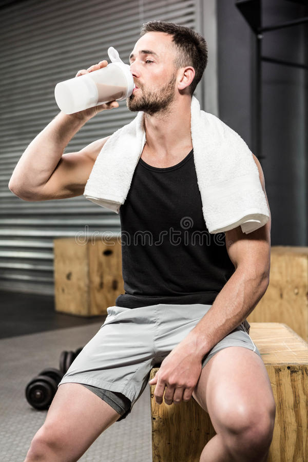 Muscular man drinking protein shake stock photography