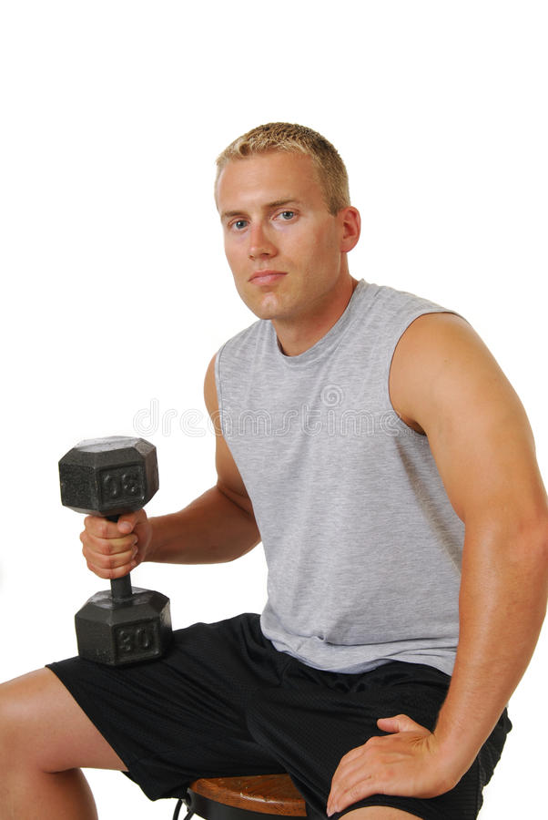 Muscular man with dumbells. A muscular young man with a set of dumbells stock image