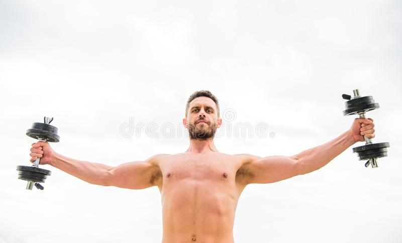Muscular man exercising with dumbbell. Dumbbell exercise gym. Sportsman with strong torso. Gym equipment. Fitness and royalty free stock photos